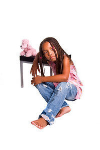 Little African American girl with finger braids and attitude sitting against a table with a stuffed animal