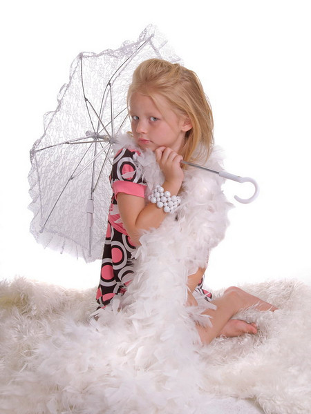 Little blonde haired girl sitting bare foot in in a pile of white feathers and fur with a white lace parasol