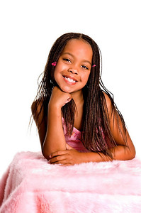 Smiling little African American girl with finger braids with her elbows on the bed