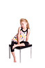 Little blonde haired girl sitting bare foot in black tights and a pastel polka dot top