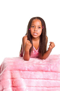 Frustrated little African American girl with finger braids shaking her fists with her elbows on the bed