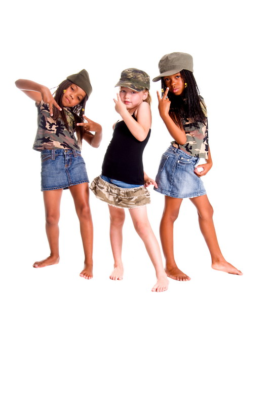 Two African American girls and one Caucasian dressed in denim skirts and military woodland camouflage tops and caps flashing peace signs