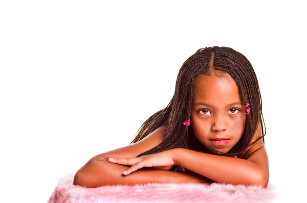 Little African American girl with finger braids with her arms crossed under her chin on a pink fur balnket