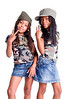 Two little African American girls dressed in denim skirts and military woodland camouflage tops and caps flashing peace signs