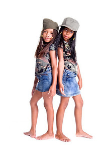 Two little African American girls dressed in denim skirts and military woodland camouflage tops and caps