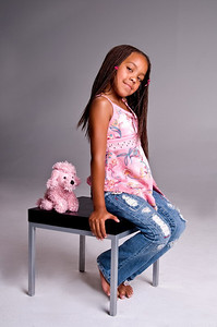 Little African American girl with finger braids sitting on a table with a stuffed animal