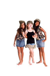 Multi racial trio of girls dressed in denim skirts and military woodland camouflage tops and caps and holding hands