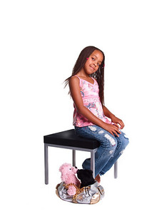 Little African American girl with finger braids sitting on a table with a purse of stuffed animals at her feet.