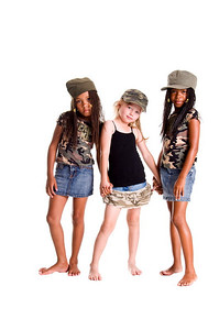 Multi racial trio of girls dressed in denim skirts and military woodland camouflage tops and caps holding hands