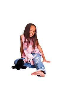 Little African American girl with finger braids sitting on the floor with a stuffed animalsat her feet.