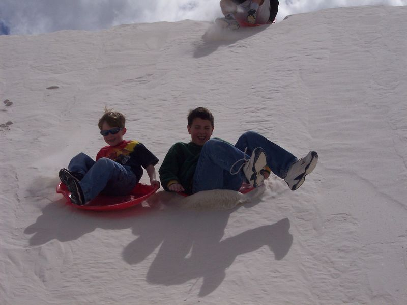 Ryan & Indy sliding down a sand dune at White Sands National Monument; March 2005