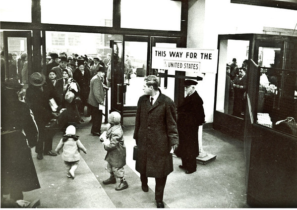 Immigration - 1957  - First picture of me in the United States - that's me in the center in the funny coat and hat with my left shoulder facing you.  Ed, Mom and Dad are just walking through the doorway.  Dad is the guy with the black hat, standing beside Mom.