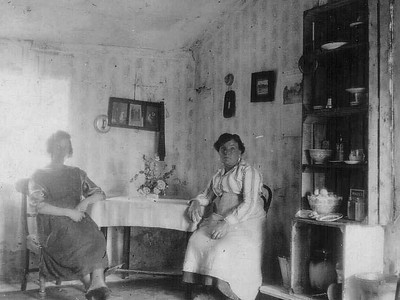 "DPB-106: Inside view of  ""The ""Bogs'  Aghalee pictured in 1920s. This was the first holiday home a few miles from the centre of Aghalee on the Soldierstown Road. Cissie McKeown (Mum's sister) and Emily McKeown (Mum's mother). Notice the onion box on right, sitting on butter box, used as dresser."