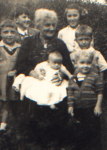 DPB-08: Emily (Granny) McKeown with Mavis Gorman on knee. Barbara , Trevor and Kenneth Gorman, Billy and James (Jimmy) Patterson. 1948 in the backgarden at 203 Cupar Street, Belfast
