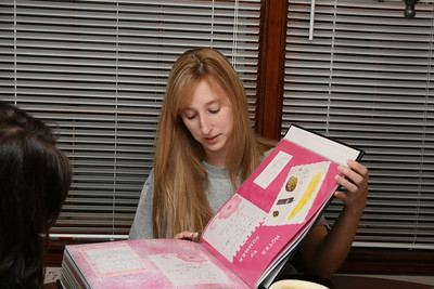 Kelly showing Cara new stuff in the scrapbook.