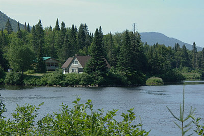 Cabin from across the river. The cabin in the foreground sleeps about 12 people.