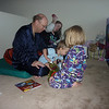 Grandpa Allred and Evelyn are helping Paul unwrap a birthday gift - a dvd of Mater's Tall Tales.