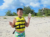 Jonathan shows off his conch shell on the beach.