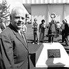 Dean Kopp in front of the Bent Monument with a plaque honoring him.