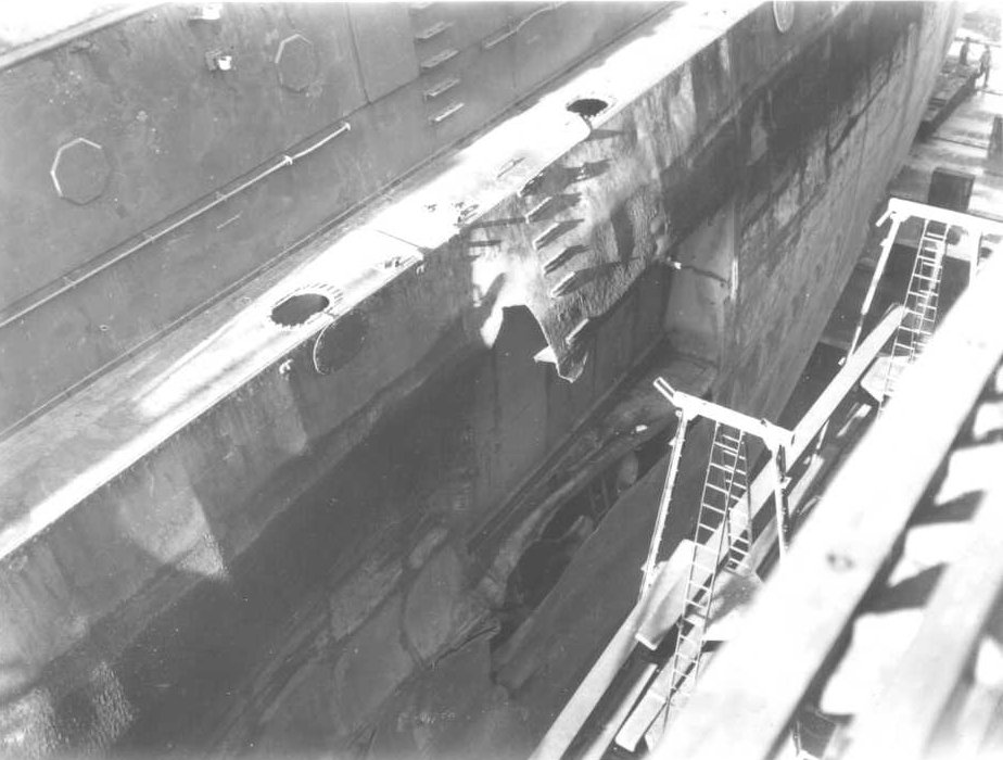 "Kamikaze (wind of god), that hit the ship in the ""blisters.""  Blisters were the doubled hull part of the ship at the waterline designed for situations just like this.  Damage in dry-dock in Guam."