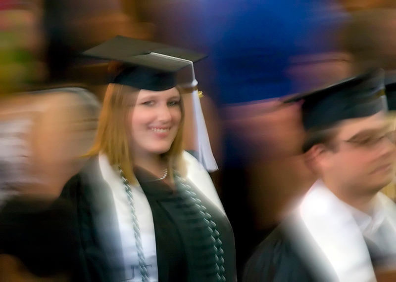 Walking out after graduation as she spots her parental units in the stands.