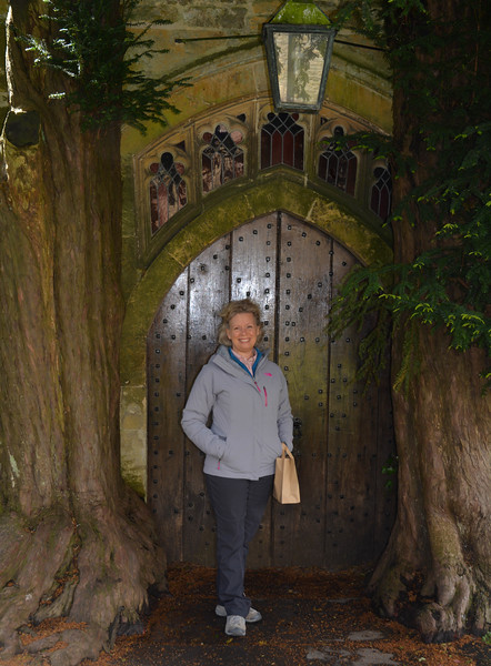 Karen by a church door bordered by 2 large trees, The Cotswolds, England.