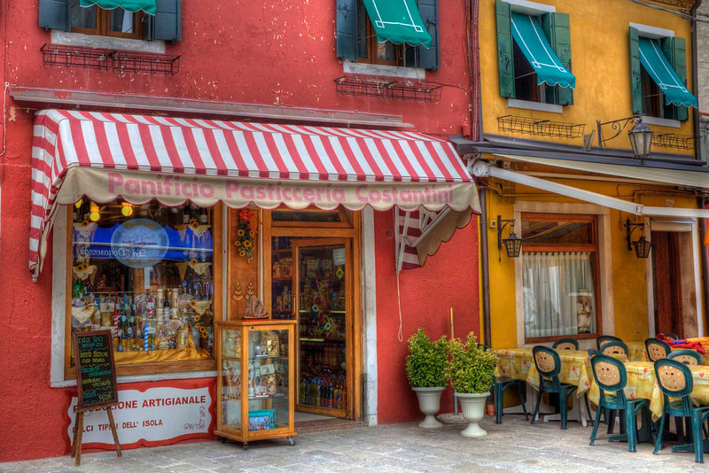 """Island Pastels from Burano, Italy<br /> A small island not far from Venice is a town of many colors. Each home and business is painted a different color. The rainbow effect splashed down on this favorite spot of  mine. Anytime we go to Venice we try to take a water bus over to this quaint little place that beckons tourist to spend a little time, spend a little money and photo buffs like me a chance to go crazy clicking a way. Beautiful restaurants on the canals and a popular item here to buy and watch artisans hard at work on, is """"lace""""."""