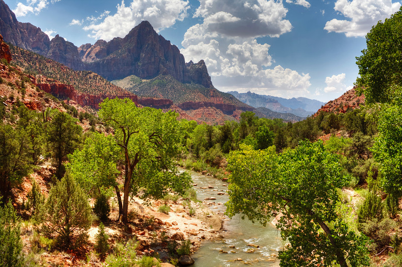 Virgin River and The Watchman, Zion National Park, Utah<br /> Very famous photo spot in Zion National Park. To get the shot you have to play chicken with the tour busses coming across a bridge you're standing on, that has no room for you and the bus. I always use a tripod, so as soon as you get your shot framed up and a bus is approaching, you have to hurry up and fold in your tripod and squeeze in at the edge of the bridge and just hope for the best. Obvious they don't want you there, but wer'e photographers, we're persisitent and sometimes, always, a bit foolish!