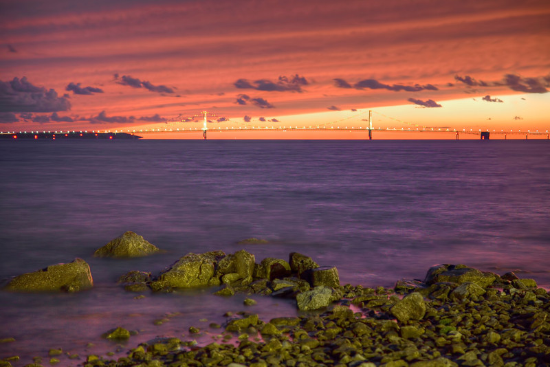 """Mackinac Bridge from Mackinac Island, Michigan<br /> Every evening tourist flock to the west shore to watch the sunset over Mackinac Bridge to the west. Lake Huron stretches out like an ocean, so big you can't see to the other side. Imagine in the winter, when all tourist have left, this lake turns to ice. For locals, it connects the mainland to the island, and snowmobiles take to the water, or should I say ice, and the boats are dry docked. After Christmas, they line up all the Christmas trees, across the lake as guiding post for the snowmobiles to follow. Pretty clever! I guess the big question each year is; """"who is the brave one to test the ice first"""". If you're wrong, goodbye snowmobile and maybe goodbye you!<br /> <br /> This photo was taken in mid September this year. We like to visit areas past tourist season. Rooms are easy to find and at a great price. We stayed in a beautiful B&B, we called the day of arrival and got it for $85.00 per night. Not a bad price and the place was fabulous."""
