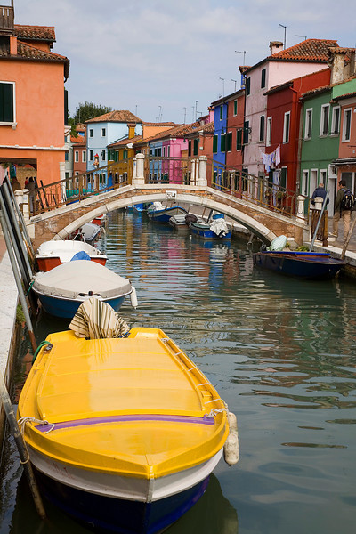 """Yellow Boat in Burano, Italy<br /> I was taking my chances of ending up in the """"drink"""" in Burano with this photo. You can see by the photo, that I leaned way to far over the water, to get the boat as much in the photo as I could. Any farther and I was in the canal. It's kind of crazy when I look back, expensive camera and all, would never survive the splash. No one ever said photographers weren't a little crazy. But, I got the shot!"""