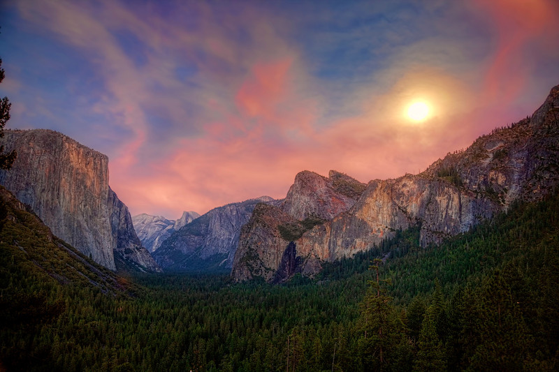 """Full Moon over Yosemite Valley<br /> Just got back from a 3 day trip to Yosemite National Park, California.  Been quite a while since my last visit, so it was time to return. I picked a great time to go with the full moon dominating the evening sky, but picked a bad time for catching the Yosemite Falls, which was dry at this time of year. I like shooting at twilight and/or the """"golden hour"""". It was interesting my 1st day reaching this point at a vista above Yosemite Valley. The skies started out quite gray with a huge thunderhead over the Sierras, with no prospect of an exciting colorful sunset, as most of the 20 or so photographers, who were lined up, were murmuring. I knew the full moon was buried under those clouds somewhere and just maybe it would all break loose and shine through. The photographers seemed to be all on the same frequency, all packed it in and left except for me and another guy. Within 30 minutes the sky opened up and the moon shined through, along with remnants of red hues from a setting sun. Like a fishermen waiting patiently for a bite on his line, the fish took the bait and it was time to reel 'em in, and we reeled in some good shots..worthy of the wait. So a message to you photographers about the """"golden hour"""", don't leave too soon..wait!!"""