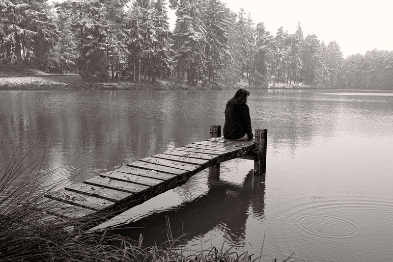 """Sittin' on the Dock of Snowy Pond in Germany<br /> Returning on the """"Romantic Road"""" from Neushwanstein Castle in Germany, we found this neat little dock on a pond. My wife wasn't that excited about jumping out of the car, into the cold, sit on a wet dock, with it snowing. But I saw an opportunity to spice up an already incredible scene, with a personal touch. When I went to the limit and ask that young beautiful woman to splash the water with her foot, for a cinemagraph, I pushed her to the limit of cold. I had a lot of warming up to do. Nice memory."""