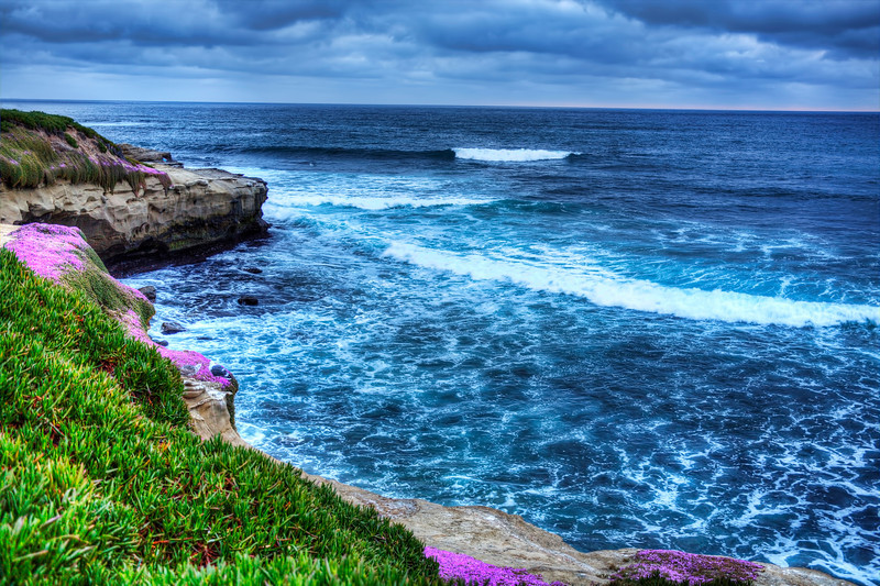 La Jolla Cove, California<br /> The  grassed park behind me was bustling with activity with families enjoying their kids, frisbee's buzzing through the air, joggers, bicyclist and rollers bladers sucking in the fresh air as they rolled by.  You would never know how busy it was, from looking at the serene cliffs, covered with flowers and sandy coves. I guess below me were the curious explorers checking out the knooks and crannies and cliffs and caves that existed along the La Jolla coast. For me, finding a clear moment to shoot a lovely shot of a beautiful sunset was all that was on my mind. The sun faded off behind the clouds, never to appear, but still made for a lovely shot over the Pacific Ocean.