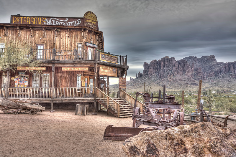 """Goldfields Ghost Town, Apache Junction, Az-The Superstition Mountains hang majestically over Goldfield's Ghost Town in Apache Junction, Arizona. One of the rare days last month where the cloud cover created some dramatic results for HDR photography. When clouds come in Arizona I go looking for a photo """"op"""" somewhere. Goldfield's offer alot of opportunities to grab texture in the old rusty cars, trains, western-style distressed wood buildings and old mining equipment. If you're  ever in Arizona, it's worth checking out. They have a great steak house I am told."""