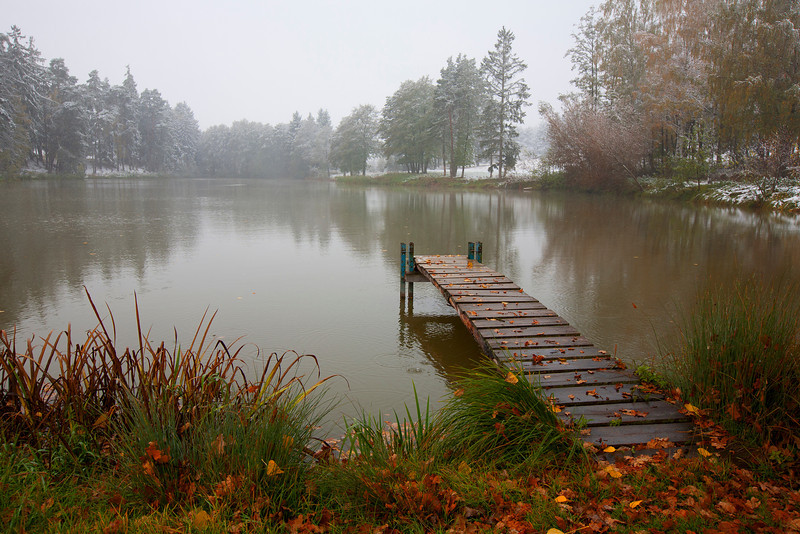 """On Snowy Pond, Germany<br /> It's hard to tell, but it's snowing. To a lot of folks, that's not impressive. But to us, having a snowy day on the """"Romantic Road"""" in Germany last fall, was quite fun. Autumn had set in nicely with everything in blazing color, and then the powdery white blanket, finished it off. This little dock was the perfect find. I shot at numerous angles trying to get just the right shot. I didn't want to leave, but the cold and getting wet finally moved me back to the vehicle. And off we went, on back roads, trying to get lost in this wonderful wanderland."""
