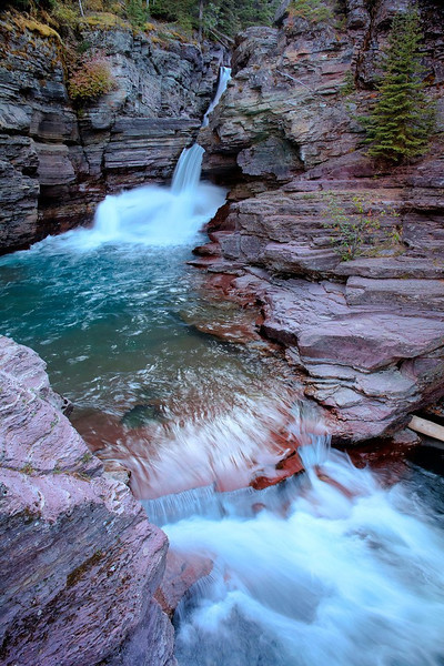 St Mary Falls, Glacier National Park<br /> It was getting near sunset and I had my doubts about trekking on a 1 mile hike out to St Mary Falls, alone. This is Wyoming, wild bear country and I have a fear about bears. I've run into them face-to-face before, seen them on many trails and I'm not fond of it. I never ventured out this late in the day, but I knew this would be the perfect time to catch a good shot of the falls. An Asian couple was speeding by me and I ask if I could tag along. We made it to the falls in record time. They wanted to snap a quick picture and head back. I convinced them to hang out for a little while so I could get my gear set up and snap a few different perspectives. They lasted for about 5 minutes and I did not want to be left behind, so I packed it in and we headed back. It doesn't take much to spook yourself when you're traveling alone. This stop was late in the season and they were closing Glacier National Park for the winter in just a few days. I was on a 6000 mile, two month journey to hit all the National Parks in the Northwest, including some in Canada. I kept moving south and autumn was coming in full bloom. I'll share some of those another time.