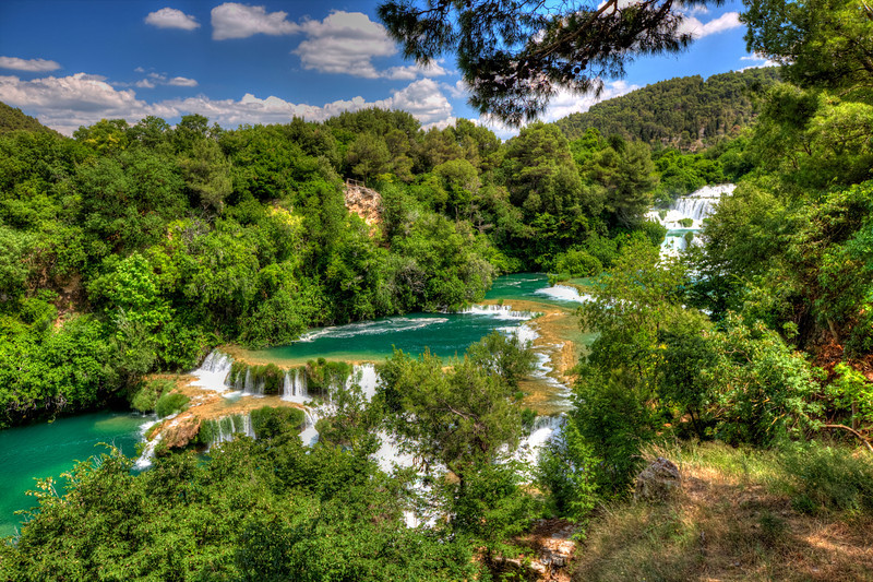 Krka Falls Croatia-Imagine a place where you can walk up to the falls and wander along it's grassy banks for what seems like a mile, and then swim at the bottom under many falls coming out of the hills all around you. Just straight east of Venice across the Adriatic Sea is Croatia. About an hour trip out of Croatia takes you into a National Park where Krka Falls is located. If you ever get to Croatia, put this one on your list. I think it's one of the most beautiful falls in the world.