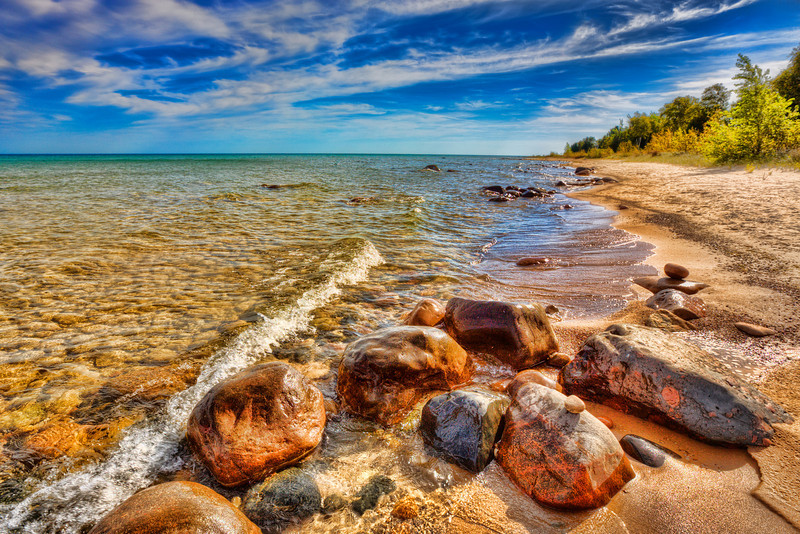 Rocky Shores of Lake Huron, Michigan<br /> On our trip to Mackinac Island we followed the west shoreline of Lake Huron for just this reason, to hopefully catch stretches of shoreline that were pristine and endless. This golden shore accented by the setting sun and a little photoshop magic helped set the mood I was hoping for.