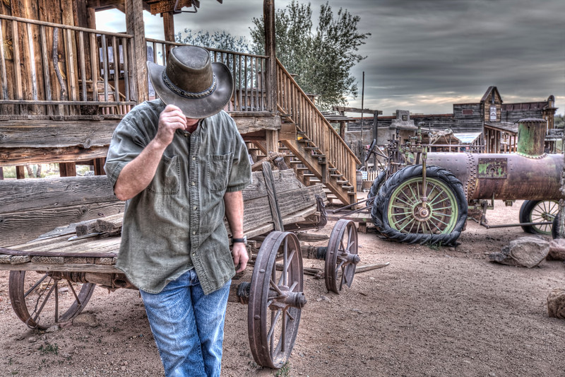 """Cowboy at Goldfields Ghost Town, Arizona<br /> Well, not really. It's just one of those rare moments I took a photo of myself pretending to be a cowboy. Though I spent most of my life singing country music and touring the country, I've since retired and enjoy seeing what I look like with a little HDR magic.  While doing this, I started attracting a crowd with alot of questions on what I was doing and why I was taking multiple shots. It's bad enough taking pictures of yourself, and then have everyone curious. I was answering alot of questions and the """"golden hour"""" was approaching. It became time to move on."""
