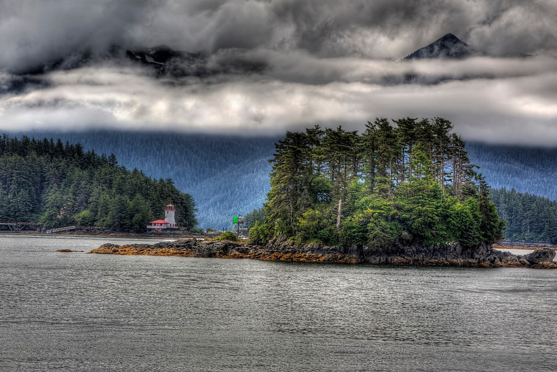 Light House near Sitka, Alaska<br /> You truly feel like you're at the top of the world, in Alaska. Everything there is larger than life, raw and wild. Heading back out to the Inside Passage from Sitka, you pass Rockwell Lighthouse. The area is peppered with small islands underneath towering mountains to the south. The cloud formations constantly moving, constantly changing, perfect for HDR-type shots. I think I could spend days traveling around and photographing this beautiful corner of the world. My second trip here and it only gets better each visit.