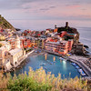 Vernazza, Cinque Terre, Italy-Overlook-I would have to say that Vernazza, Italy is probably on the top of the list for photographic vistas anywhere in the world. To climb up the steep cobblestone pathways to your own little spot, before the crowds show up at sunset, and to share that spot with a dozen other photographers is quite intoxicating. People around you from all parts of the world converging on this famous cliff-side town, all wanting the same thing..a moment frozen in time to hold onto for a lifetime. I happen to be standing next to a commissioned photographer from Japan who had a dream job. He travelled the world testing new cameras for Sony, Canon and Nikon and got paid for it. Who wouldn't want to do that. This guy was pulling out cameras like a gunfighter pulling a pistol out of a holster. It was quite exciting to watch him juggle between shots knowing he only had a few minutes with the golden sunset.