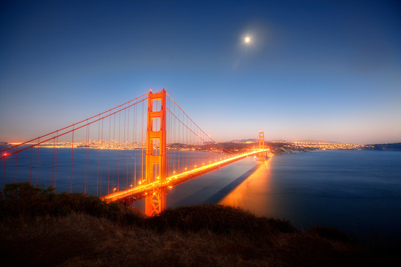 Full Moon Over The Golden Gate Bridge<br /> San Francisco is usually very foggy in August, but we lucked out with a couple of clear days. I spent a few hours at sunset on the cliffs overlooking the Golden Gate Bridge. Being from Arizona, I didn't plan on it being so flippin' cold in the evening. I ended back at the car with freezing cold hands and the heat on to thaw out. I guess I shouldn't complain to much.  Got to experience an incredibly beautiful moonlit night at one the most photographed bridges in all the world.