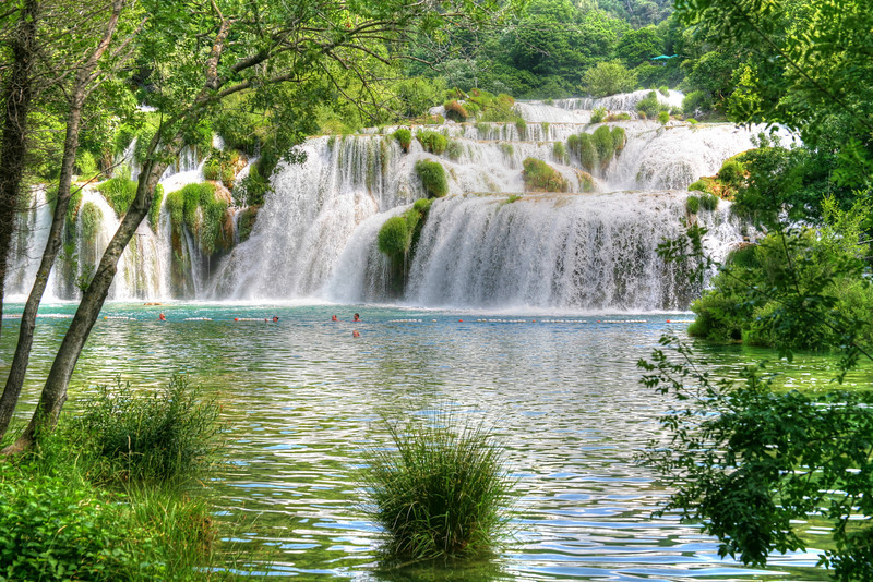 Taking the Plunge at Krka Falls, Croatia<br /> I never thought the cascades would end. We started at the top and kept following the falls all the way down. The grass was growing in the falls and all around it. I had been to alot of falls, but this one was so different and by far my favorite. It is so accessble at points along it's banks, making photography very fun and interesting. Krka Falls is located about an hours drive out of Split, Croatia, which is straight east of Venice, across the Adriatic Sea.