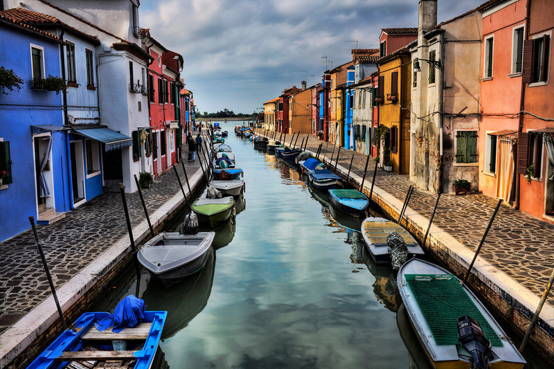 """""""Buy a Print""""-Canals of Burano, Italy-A short distance by water taxi or water bus from Venice is a cute small island called Burano. Every home is painted a different color. Like Venice canals weave through the town from every direction with many bridge crossings. This island is definitely a tourist destination with shops and restaurants up and down the cobblestone walkways and corridors. As a photographer your camera never stops clicking as the """"photo ops"""" simply unfold in front of you."""