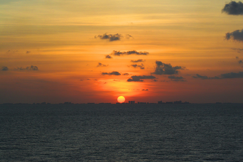 Cancun Sunset, Mexico-<br /> As we were cruising north out of Cozumel heading for the port in Galveston, I noticed a line of hotels silohuetted by the sun. It didn't hit me right away that we were passing Cancun. The next year we were sitting on the beach in Cancun looking east, the other way, seeing the ships passing in the distance. It was kind of cool seeing the different perpectives. I don't know why I bring this up. It reminds me  of a story I once heard of a man when he was a young boy, fishing in a pond, looking up at a jet passing overhead and dreaming of one day flying in an airplane. Now he's older sitting in an airplane, looking down below at the lakes and ponds, wishing he was  fishing. Dreams change, perspectives change.. Time plays with us. As much as I've traveled and flown all over the world, at the moment, fishing sounds pretty good!