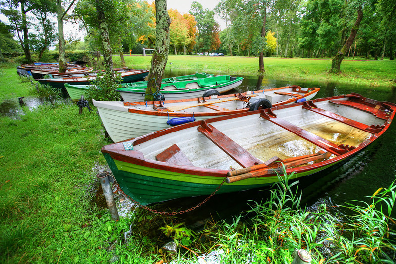 Row Boats at Ross Castle, Killarney, Ireland-I thought this was a colorful display of boats on the grounds at Ross castle. It was being the normal Ireland and raining, so photographing with an umbrella over your head was a necessity. I think the thing that grabs you in Ireland is how vibrant the greens are.  Makes me want to go back! If it wasn't for the stress of driving on the opposite side of the road, just maybe.