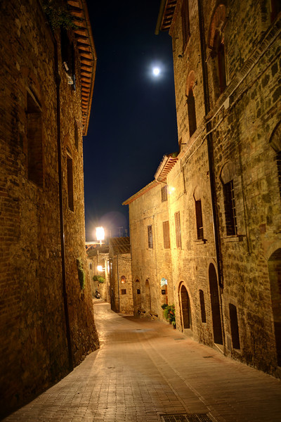 """""""Moonstruck in Siena""""-The dark corridors of ancient Italian villages and towns make for some interesting eerie HDR's. We happen to be in Tuscany during a full moon, so it just had to be in the pictures. Cobblestone streets lead out to open piazza's where you will usually find people meandering, restaurants and pizzerias buzzing and shops galore promoting their wares. Searching out dark hidden pathways made it all the more fun and exciting to try out some high dynamic range photography. The older and grainier the better."""
