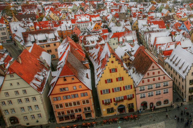 Along the Roof Tops of Rothenberg,Germany<br /> It's quite a climb through the narrow spiral staircase that takes one to the top of the City Hall Tower. I kept thinking how can these steps get any narrower and they did. By the time I climbed through what was now a hole to the top, it got pretty queasy. They would only allow a certain number of tourist up on top of the tower at a time, which was a good thing considering how cramped the space was. But wow, what a view. With fresh snow from the night before blanketing the roof tops and countryside in the distance, it was quite breathtaking. With screening all around you, finding a hole to poke your camera through was a challenge. I would definitely say, Rothenburg was one of the more scenic towns on the Romantic Road in Germany. It was snowing the 1st day we arrived, and that for us, made it even more special.