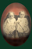 Dora (Troyer) Yoder (Milford Yoder's mother) as a baby, with her twin sister... on green background