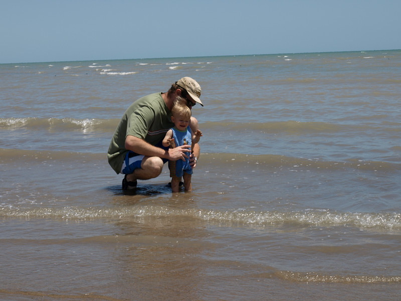 Daddy takes him into the ocean to wash off.